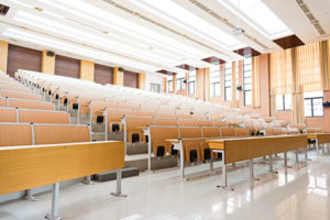 College lecture hall with large group of seats.